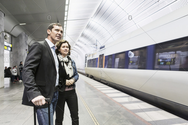 Business colleagues standing at railroad station platform