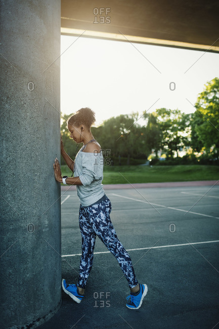Woman stretching by column on street