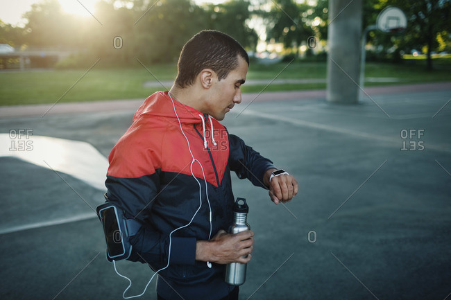 Man checking time on smart watch while standing on street