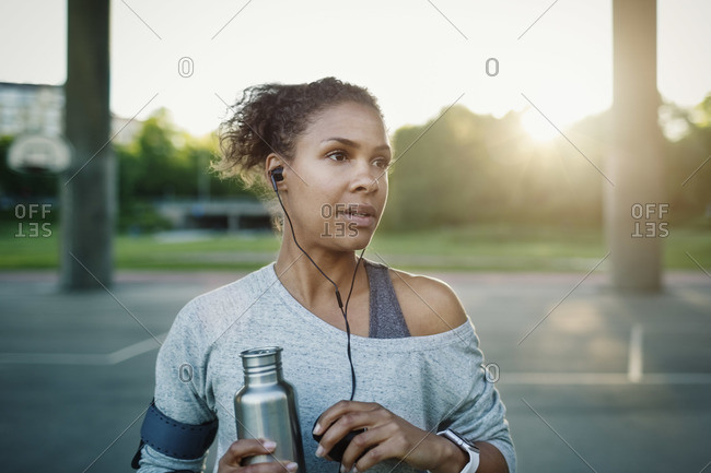 Woman holding water bottle while standing on street