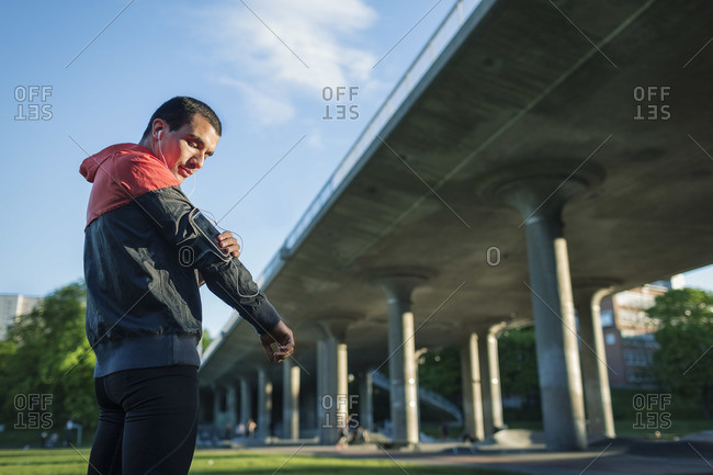 Low angle view of man touching arm band while standing against bridge
