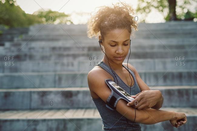 Woman using smart phone armband while exercising