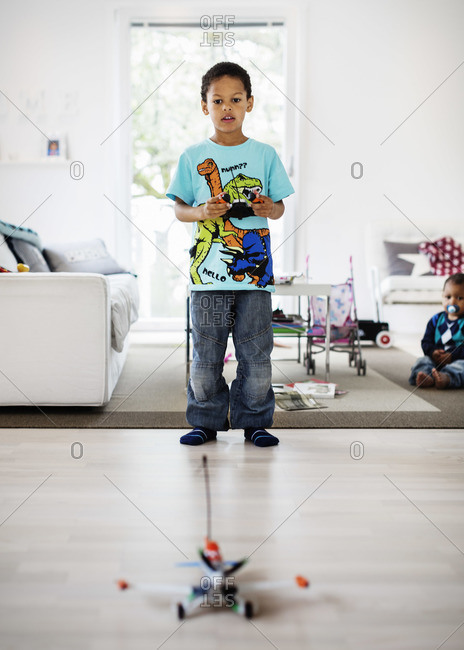 Boy playing with remote controlled airplane at home with brother sitting in background