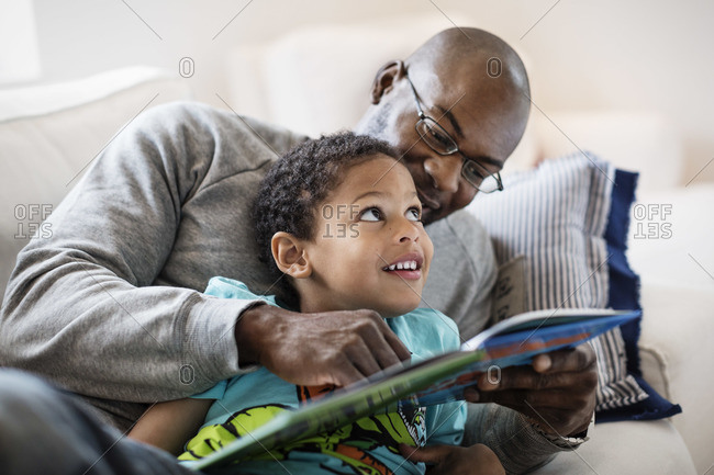 Smiling boy looking at father while reading picture book at home