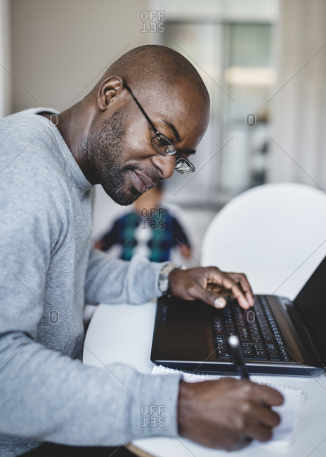 Side view of man writing while working on laptop at home