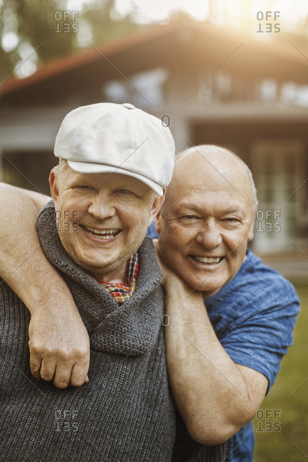Portrait of happy gay man leaning on partner's shoulders at yard