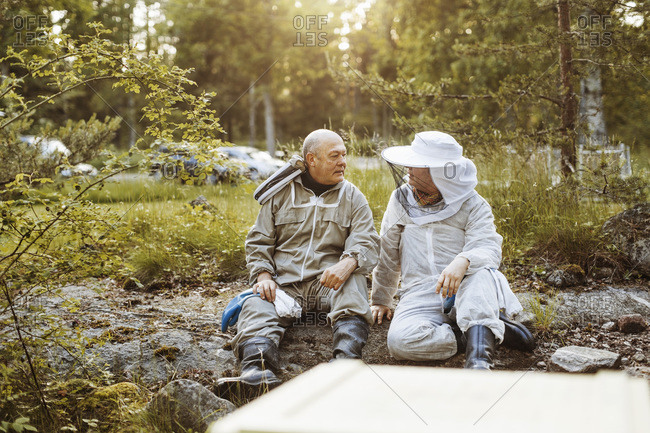 Beekeepers conversing while relaxing at field
