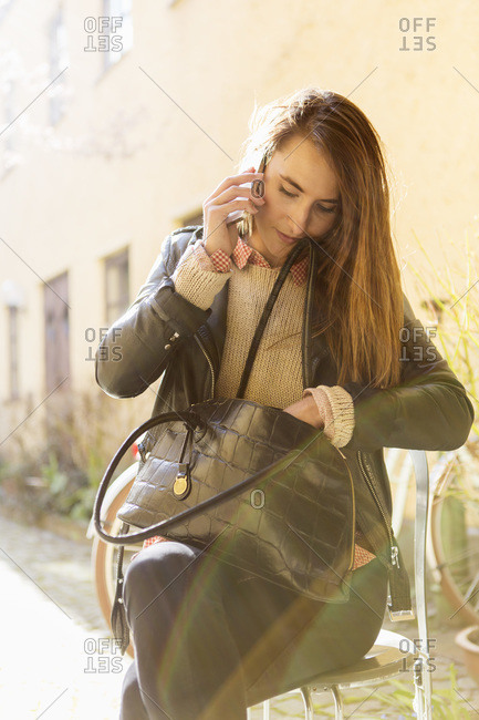 Businesswoman using mobile phone while searching something in purse while sitting on chair at sidewalk