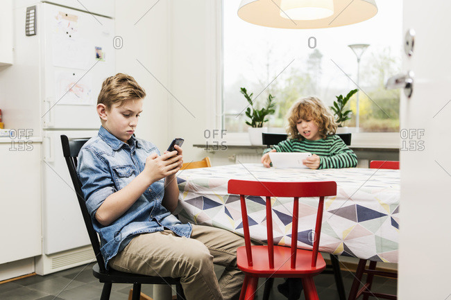 Boys using technologies at dining table in kitchen