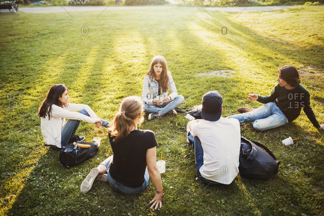 High angle view of male and female teenagers relaxing on grass