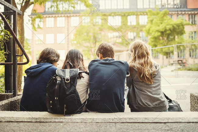 Rear view of teenagers sitting on steps outdoors