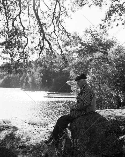 An elderly gentleman sitting on a large rock by lake