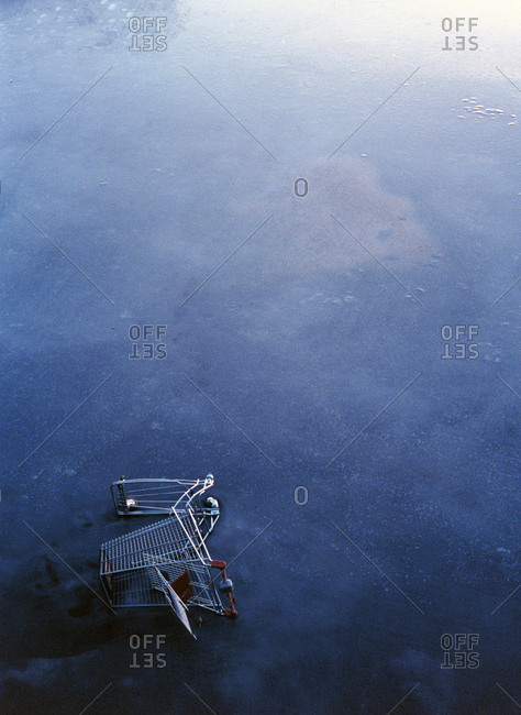 An abandoned shopping cart on a frozen lake