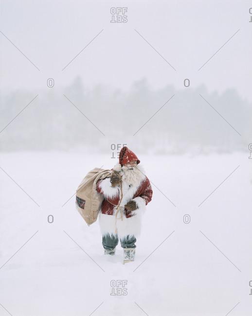 Man dressed as Santa Clause walking on snow