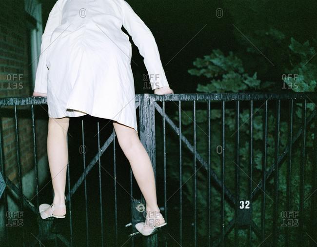Woman climbing a gate at night