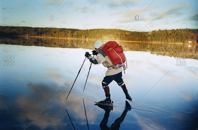 Man ice skating on frozen lake