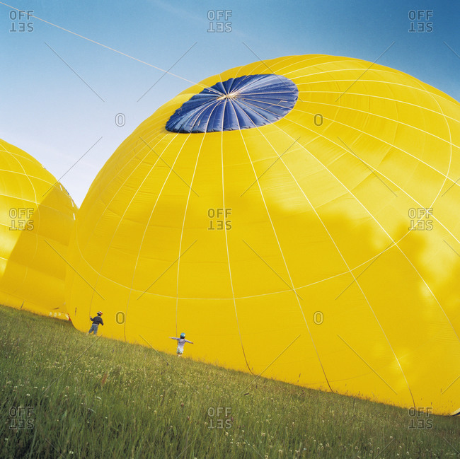 Hot air balloon rising in field