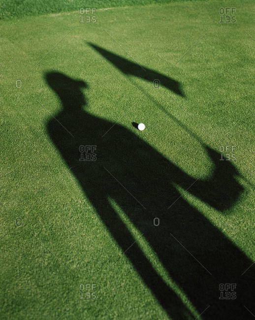 Shadow of a man holding the flag on a golf course, Sweden