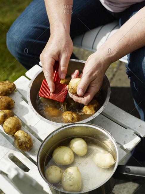 A woman washing potato, Sweden