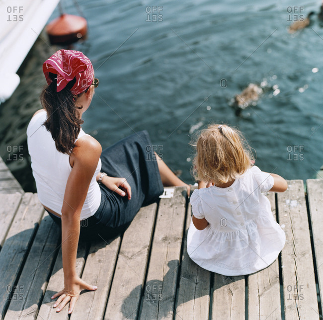 Mother and daughter sitting on a wooden jetty by lake