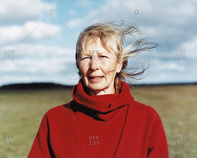 Portrait of mature lady in red overcoat standing in field