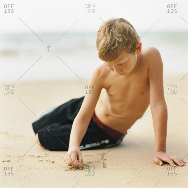 Young boy paying with sand on beach