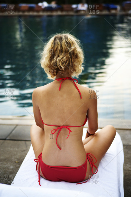 A scandinavian woman sitting by a swimming pool, Thailand