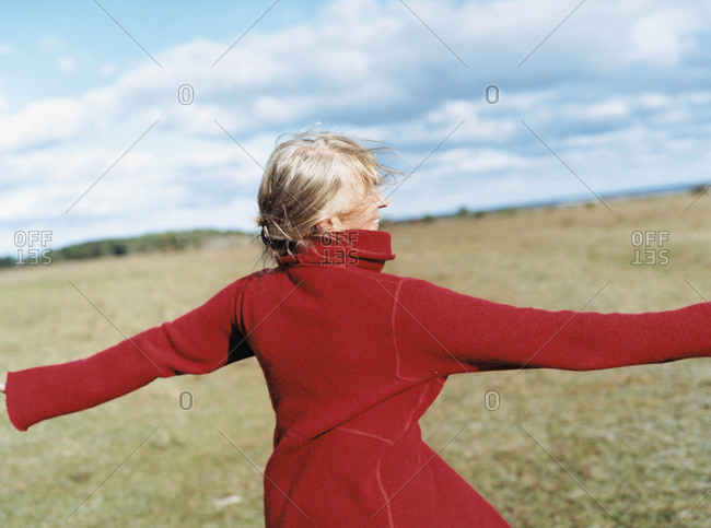 Mature lady in red overcoat with happy expression in field