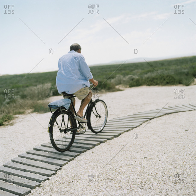 Elderly man cycling at the beach