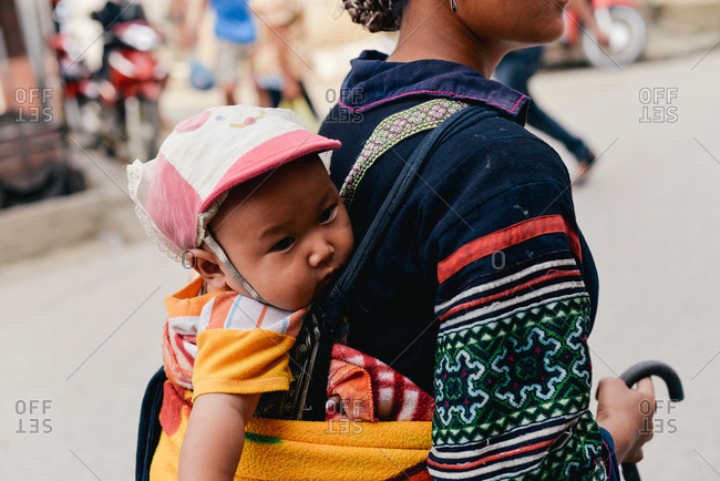 Sapa, Vietnam - July 13, 2015: A mother roams the streets selling souvenirs to support her family