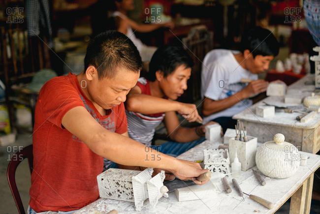 Sapa, Vietnam - July 13, 2015: Men whittle their crafts in a small village near Sapa