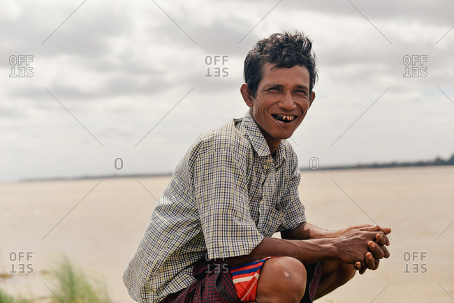 Myanmar - July 19, 2015: Portrait of  a sailor waiting for arrival of the next boat on the edge of an island