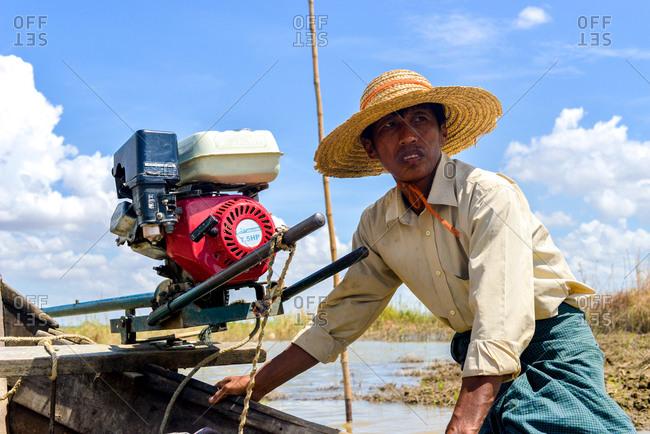 Bagan, Myanmar  - July 19, 2015: A man maneuvers a boat across a small lake near Bagan