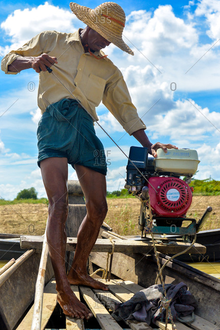 Bagan, Myanmar  - July 19, 2015: A man powers up a boat on a small lake near Bagan