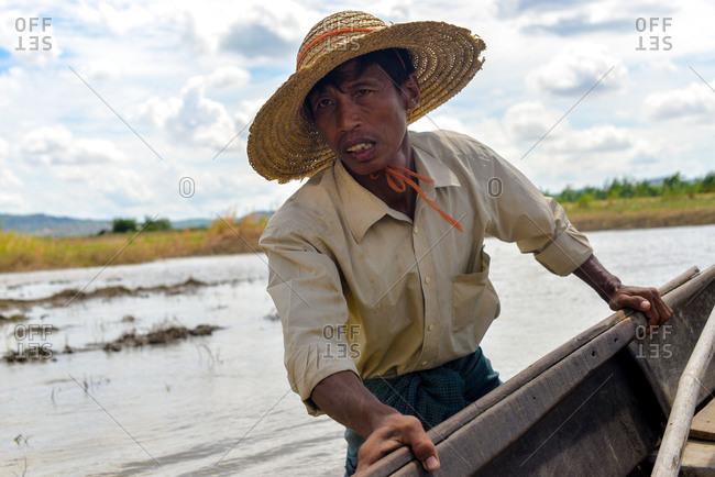Bagan, Myanmar r - July 19, 2015: A man powers a boat across a small lake near Bagan