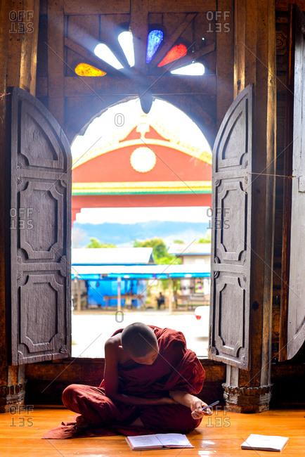 Nyaung Shwe, Myanmar - July 21, 2015: Resident monk studying at the Shwe Yan Pyay Monastery