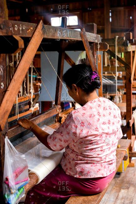 Inle Lake, Myanmar - July 22, 2015: Women weaving garments at Ko Than Hlaing Silk and Lotus Weaving