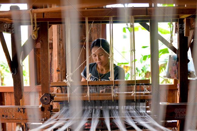 Inle Lake, Myanmar - July 22, 2015: Woman weaving at Ko Than Hlaing Silk and Lotus Weaving