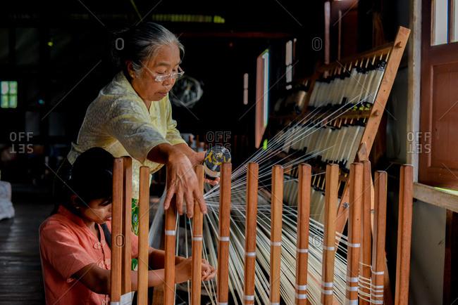Inle Lake, Myanmar - July 22, 2015: Two women weaving at Ko Than Hlaing Silk and Lotus Weaving