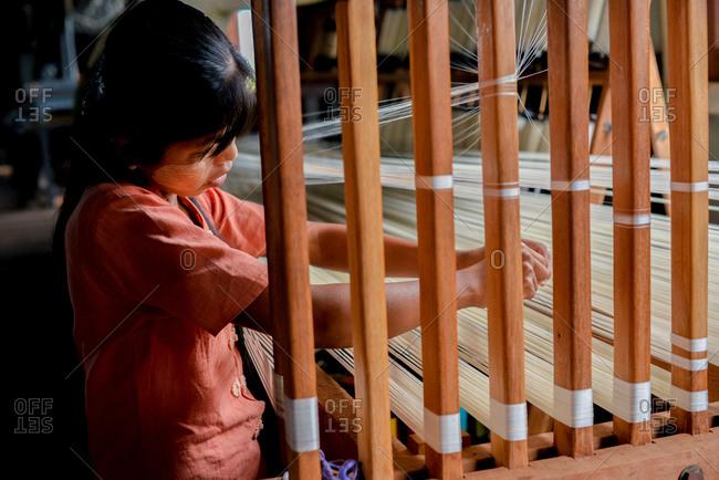 Inle Lake, Myanmar - July 22, 2015: Young woman weaving at Ko Than Hlaing Silk and Lotus Weaving