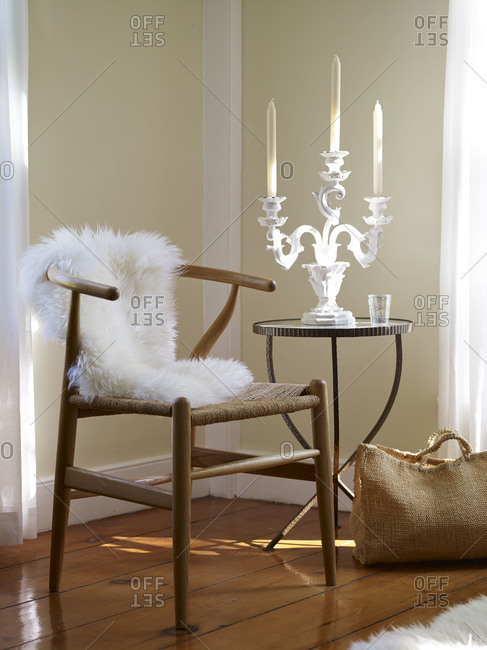 Candelabra on table by chair