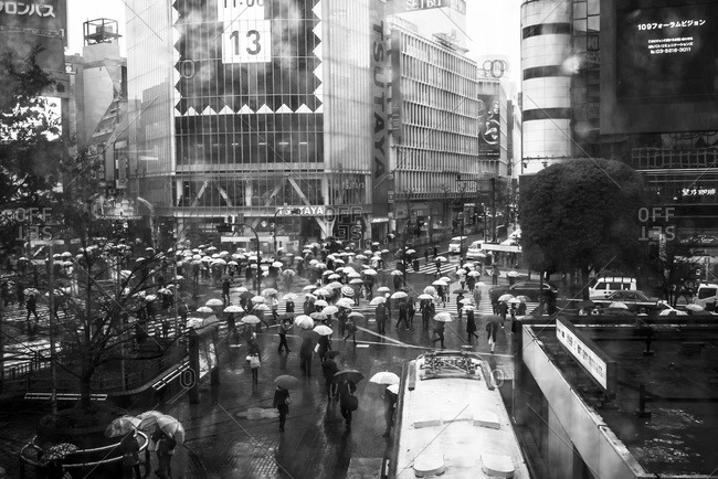 Tokyo, Japan - November 26, 2014: Crowded intersection in the rain