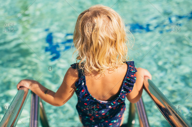 Little blonde girl walking down a ladder into a pool