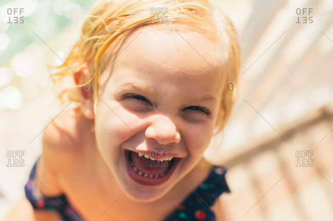 Close up of a little blonde girl by a pool