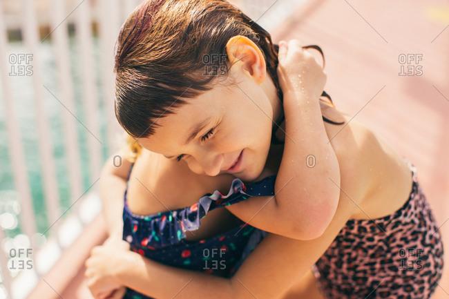 Sisters hugging beside a pool