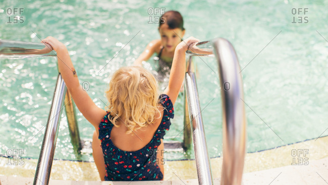 Little girl walking down a ladder into a pool