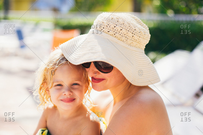 Mother in a white hat holding her daughter poolside