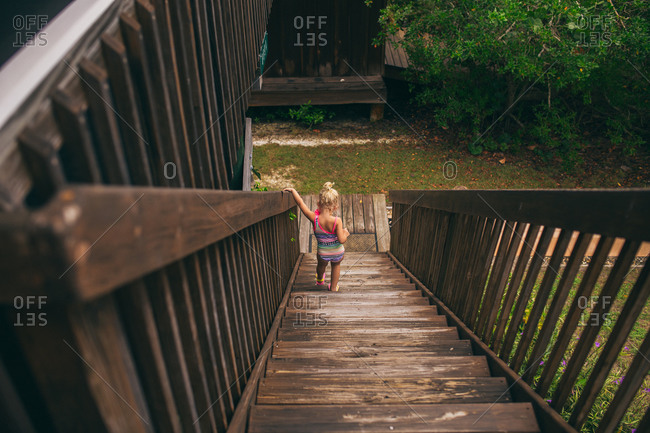 Young girl walking down wooden stairs in a swimsuit