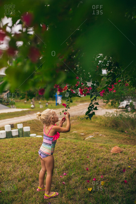 Girl in a swimsuit picking pink blossoms off a tree