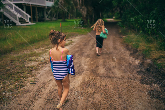 Kids walking down a dirt road in swimsuits carrying beach towels